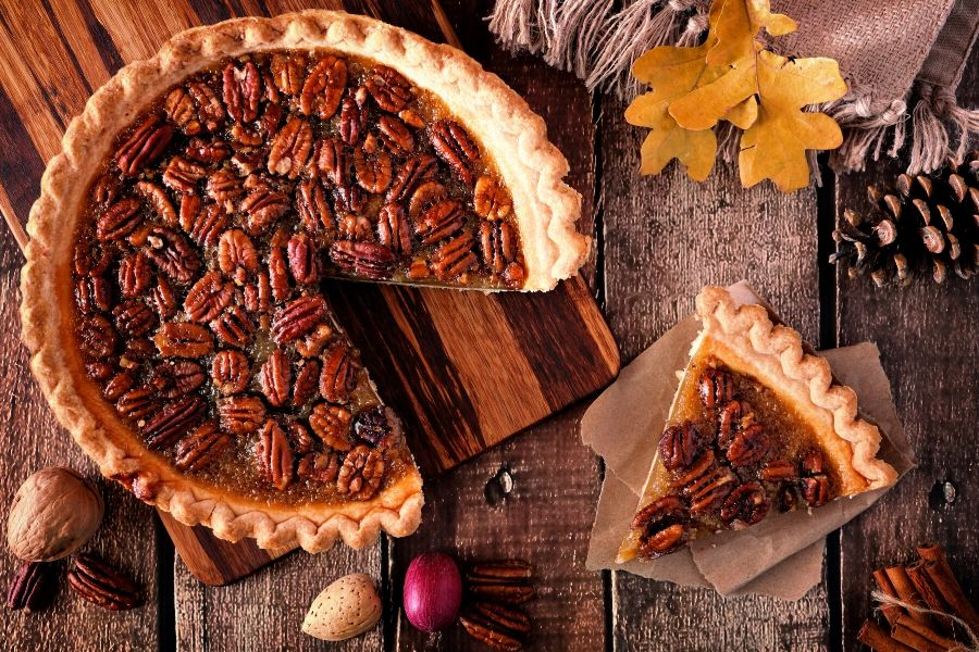 Pecan pie with slice cut out and on table