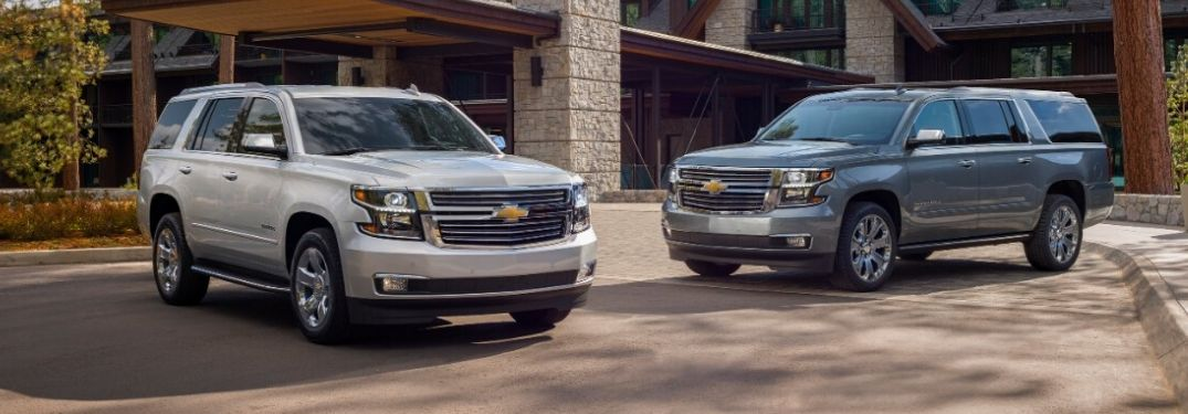 Two 2020 Chevy Suburbans in front of large house from exterior front passenger side and exterior front drivers side