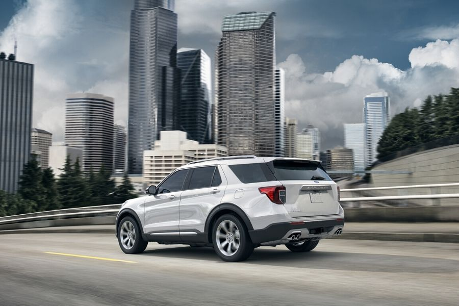 White 2020 Ford Explorer driving down city road from exterior passenger rear_o