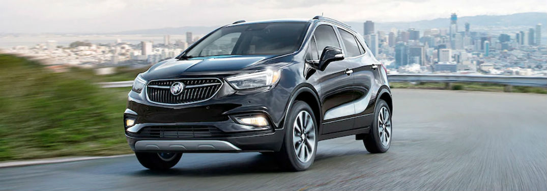2020 Buick Encore black exterior front fascia driver side driving city in far background