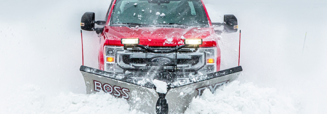 red ford truck plowing snow