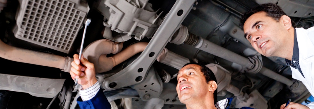 mechanics inspecting car undercarriage