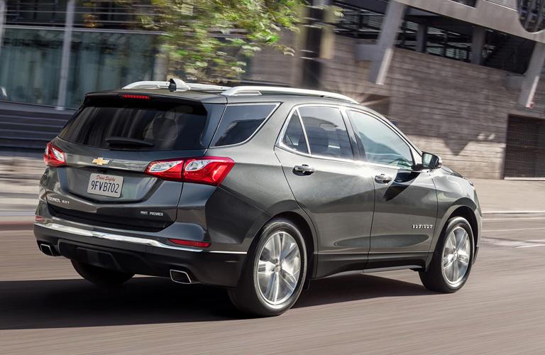 Silver 2020 Chevy Equinox drives along a city street
