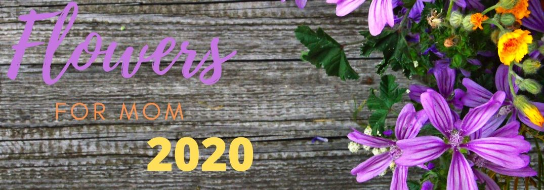 "Multicolored text reads, ""Flowers for Mom 2020"" on a background of wood with some flowers laying beside."