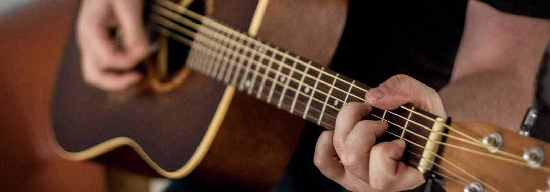 Two hands play an acoustic guitar