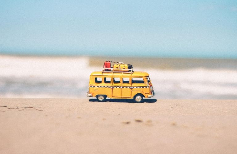 A yellow toy retro van rolls along a beach