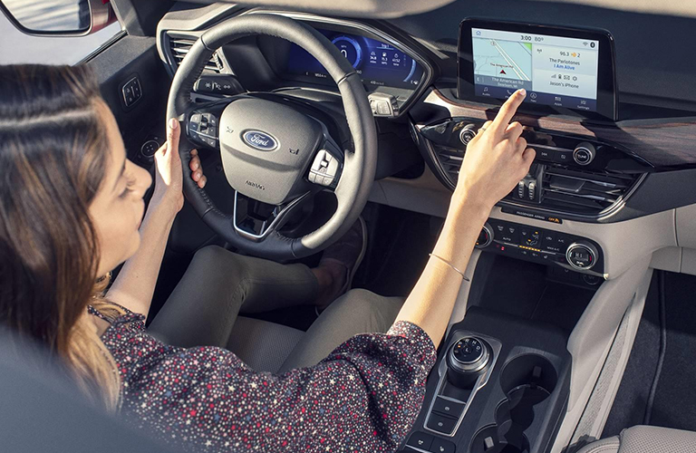 Woman interacts with the touchscreen inside a 2020 Ford Escape
