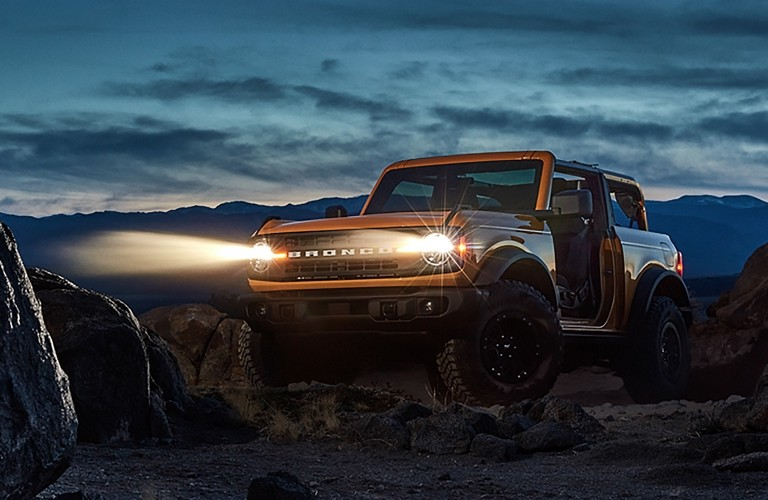 2021 Ford Bronco sits in a desert at night with its lights on.