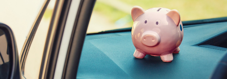 Piggy bank sitting on dashboard