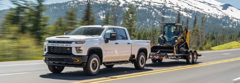 2021 Chevy Silverado HD drives along a highway with a mountain backdrop