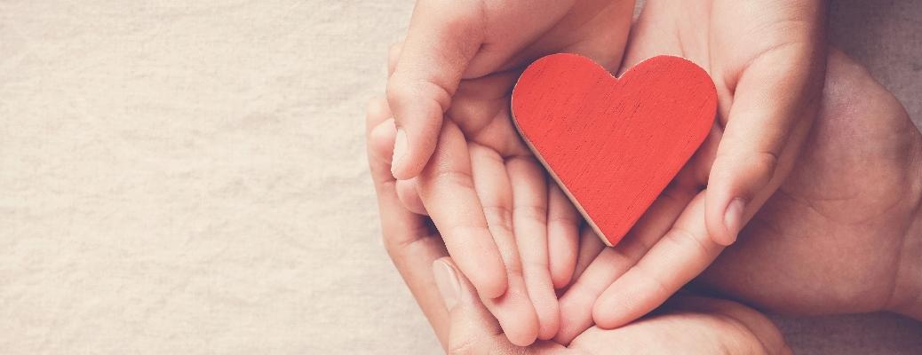 Hands cup a paper heart