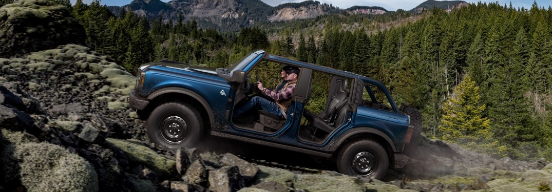 Side view of a blue Ford Bronco offroading