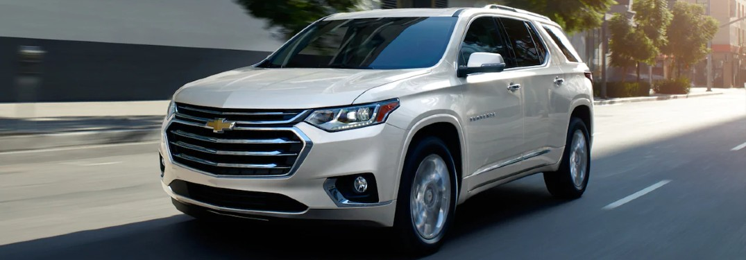 Front driver angle of a white 2021 Chevrolet Traverse driving on a road