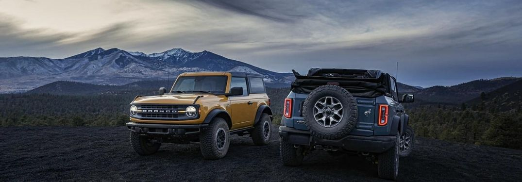 Two Ford Bronco against with a mountain in the background