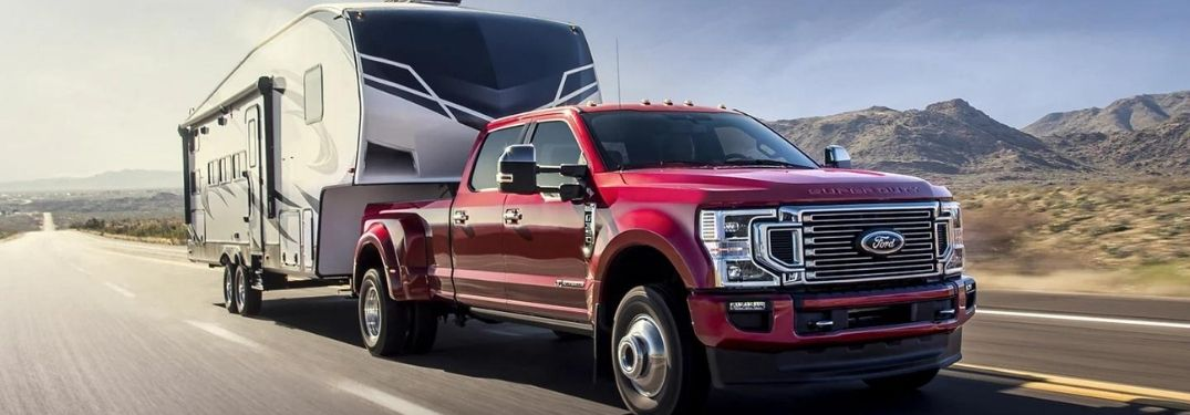 A red 2022 Ford F-350 towing a trailer.