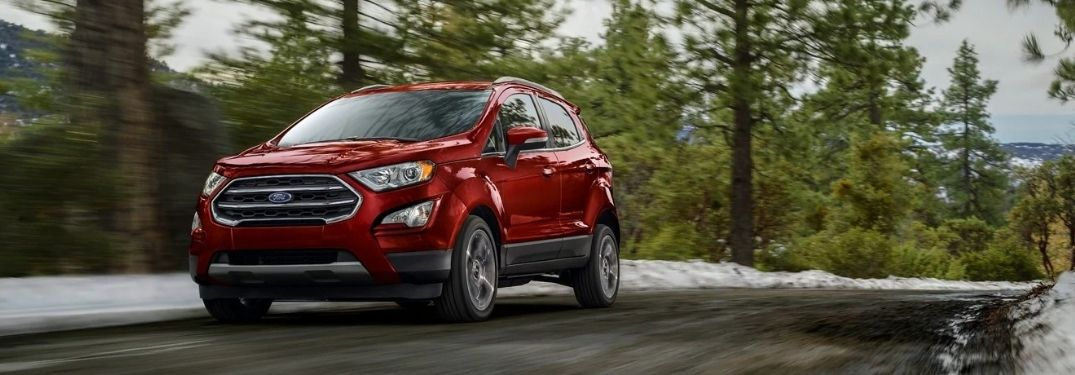 The 2021 Ford EcoSport driving on a road surrounded by trees.