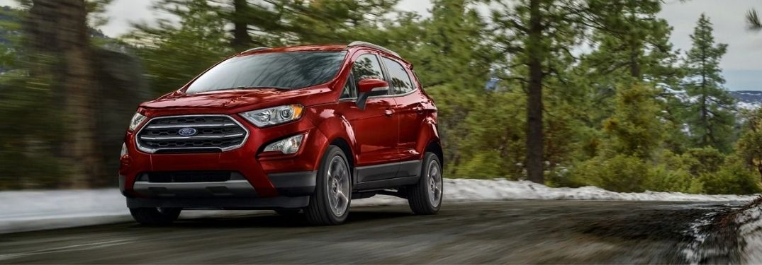 A red 2021 Ford EcoSport driving on a road surrounded by trees