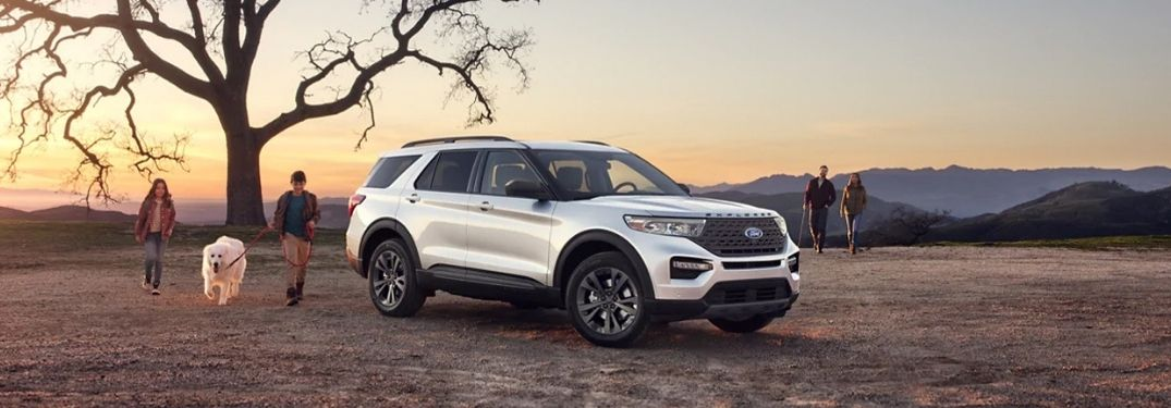 A white 2021 Ford Explorer parked by a tree.