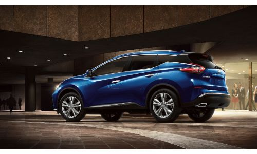 2020 Nissan Murano blue facing right showing driver side doors and some of back bumper outside building at night