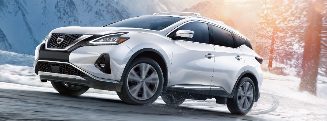 2020 Nissan Murano white paint driving on snowy road around curve with lens flare