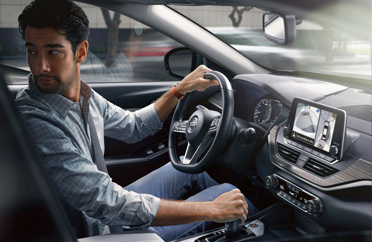 A man sitting behind the wheel of a 2020 Nissan Altima