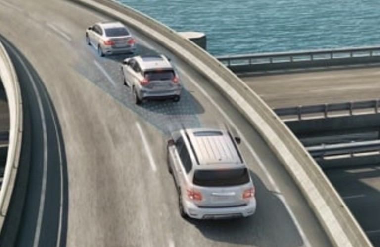 2020 Nissan Armada driving on a road with two vehicles in front of it