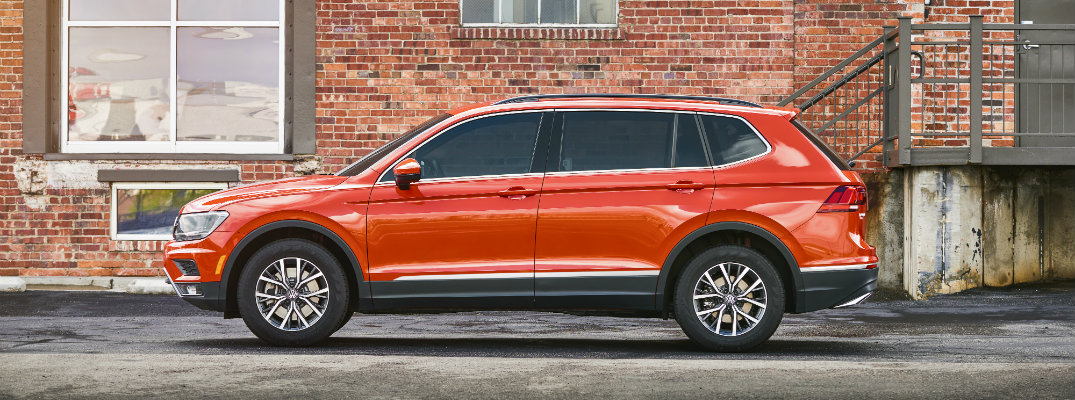 Side profile of 2018 Volkswagen Tiguan parked in front of brick building