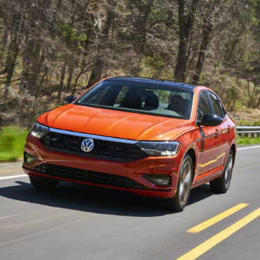 Orange-colored 2019 Volkswagen Jetta driving down a rural road
