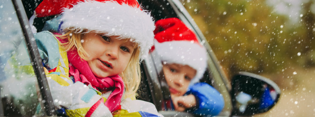 Little kids wearing Santa hats while riding in a vehicle
