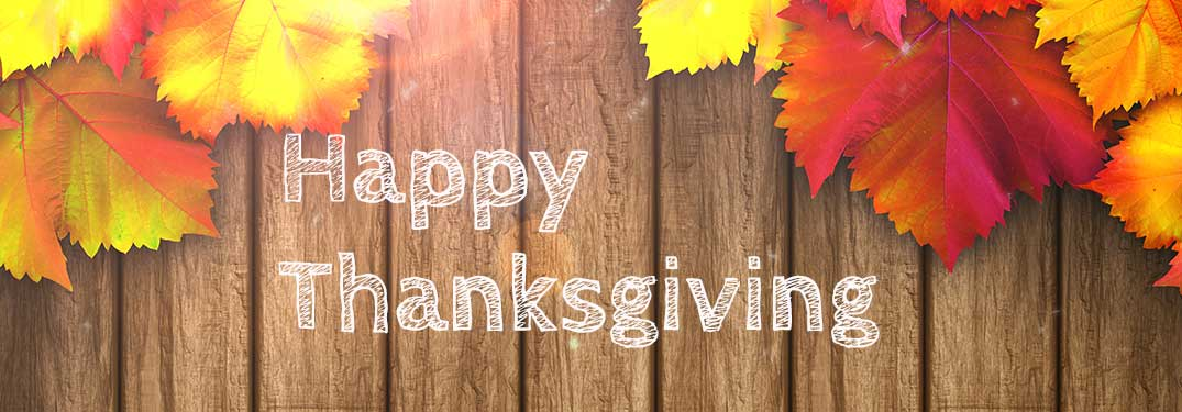 words Happy Thanksgiving on a wood-grain and fall leaf background