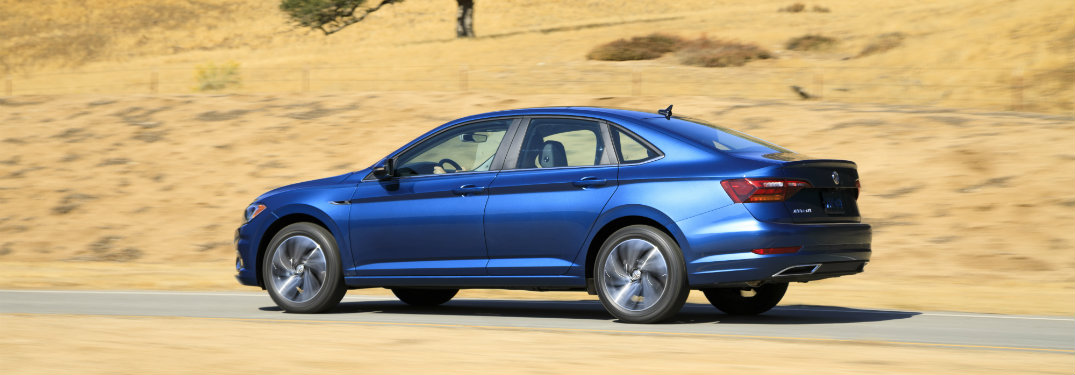 side view of a blue 2019 VW Jetta against a background of rock