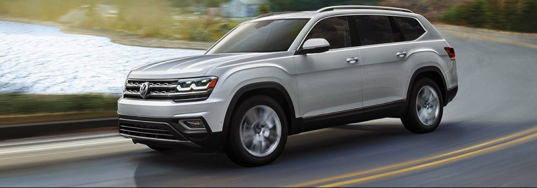 A silver 2019 Volkswagen Atlas cruises around a highway curve with a lake in the background.