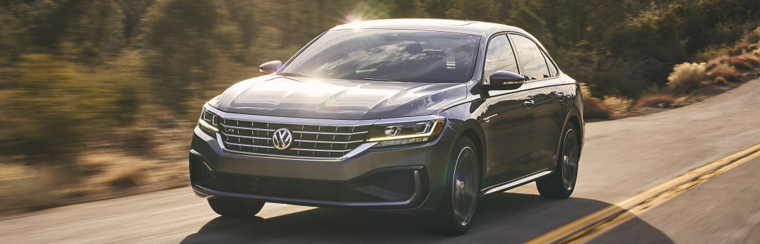 Silver 2020 Volkswagen Passat drives down the highway with the sun shining on it.