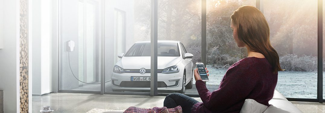 A woman looks at her phone while a Volkswagen vehicle is parked outside.