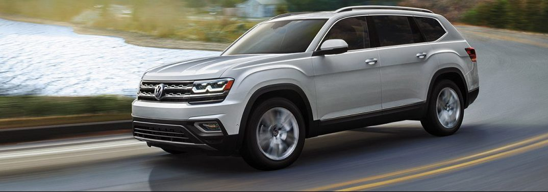 Silver 2019 Volkswagen Atlas cruises around a highway curve with a body of water in the background.