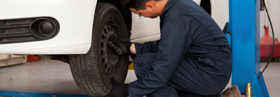 Man firmly grips tire in preparation to remove it from a vehicle in a shop, and proceed with the tire rotation process.