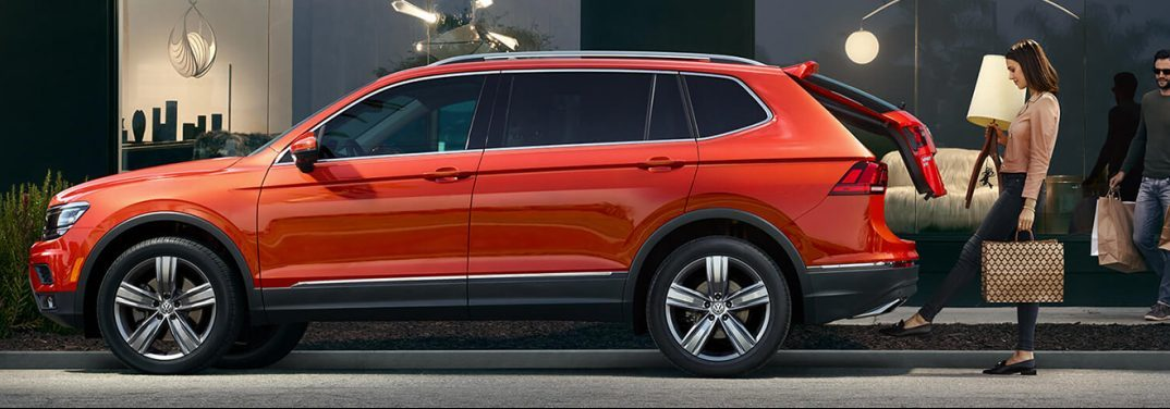 Habanero Orange 2019 Volkswagen Tiguan is parked outside a store. A woman opens the liftgate with her foot while a man brings more bags over.