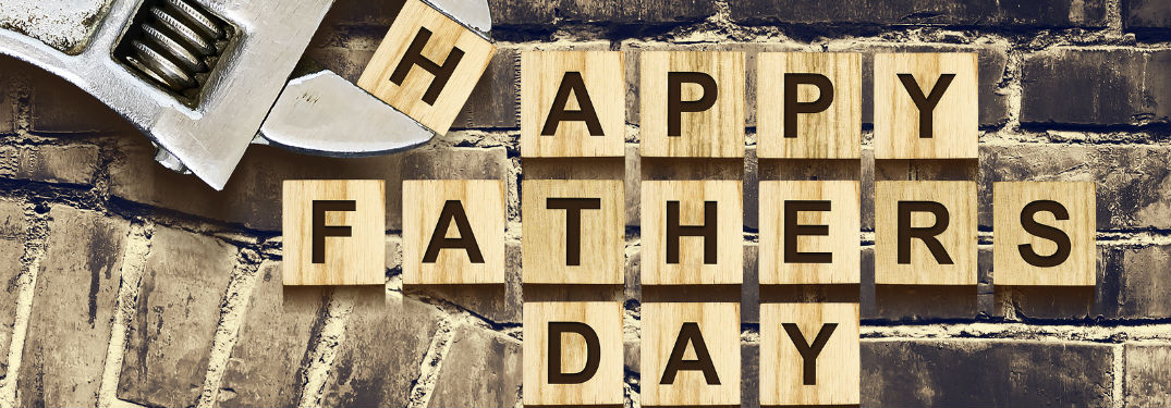 "A wrench puts the final ""H"" into place, completing the phrase ""Happy Father's Day"" spelled out on small wooden letter tiles against a brick background."