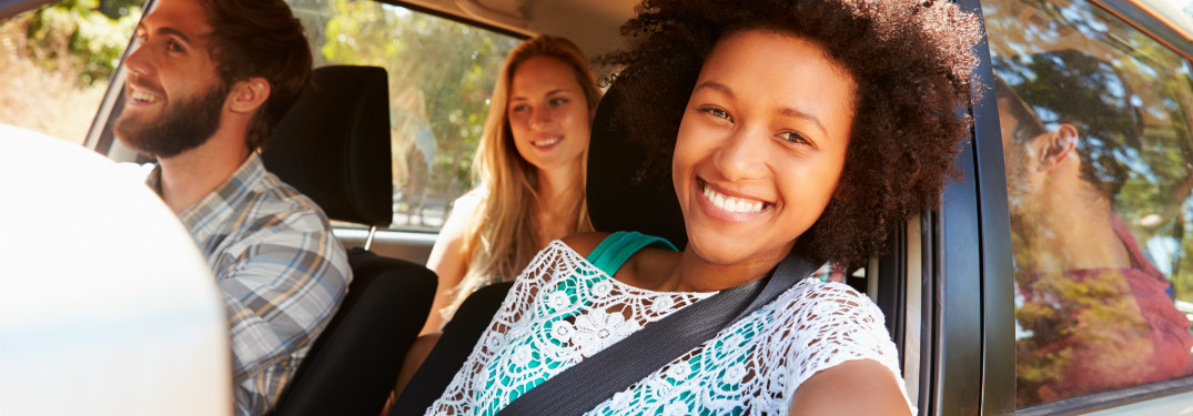 A smiling woman drives a car and prominently wears a seatbelt.