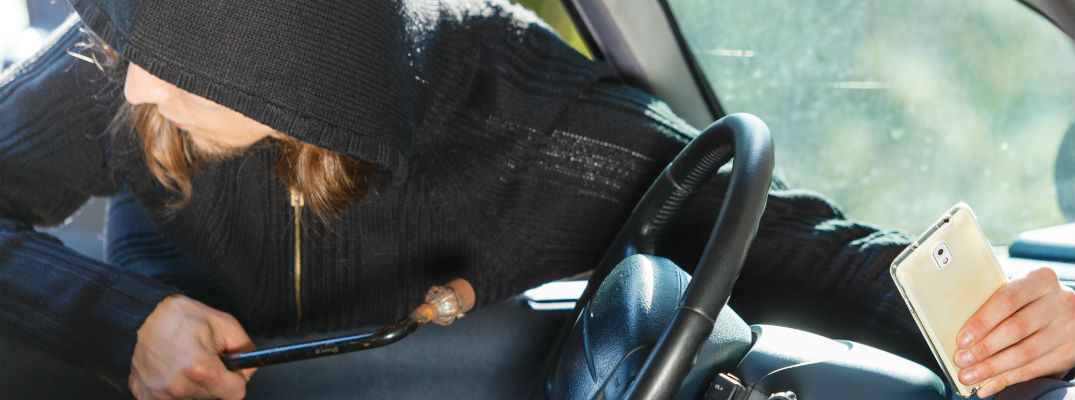 A stock photo of a person breaking into a vehicle.