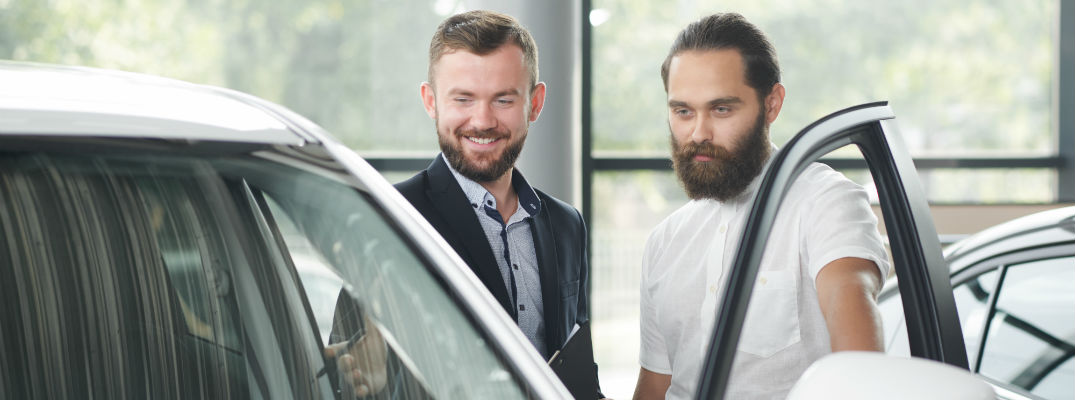 A stock photo of a person looking at a new vehicle with a salesperson at a dealership.