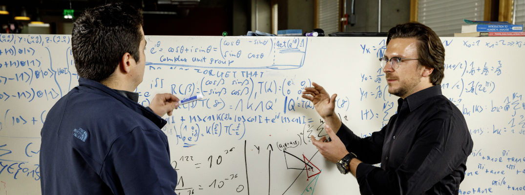 A photo of two people working on math equations on a white board.