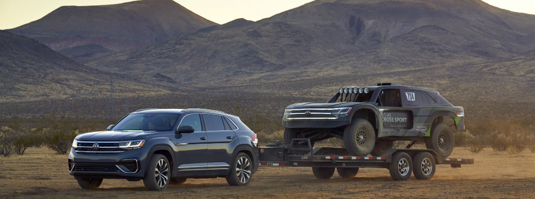 A photo of the Volkswagen Atlas Cross Sport pulling the rally racing version of the vehicle.