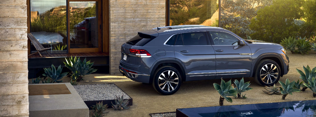A right profile photo of the 2020 Volkswagen Atlas Cross Sport parked in front of a house.