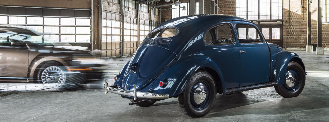 A photo of an original Volkswagen Beetle parked in a garage.