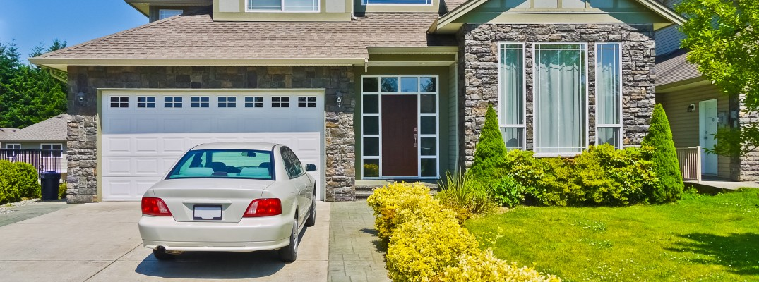 A stock photo of a sedan parked in a driveway.