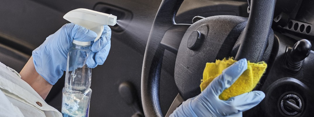 A stock photo of a person cleaning a car's steering wheel.