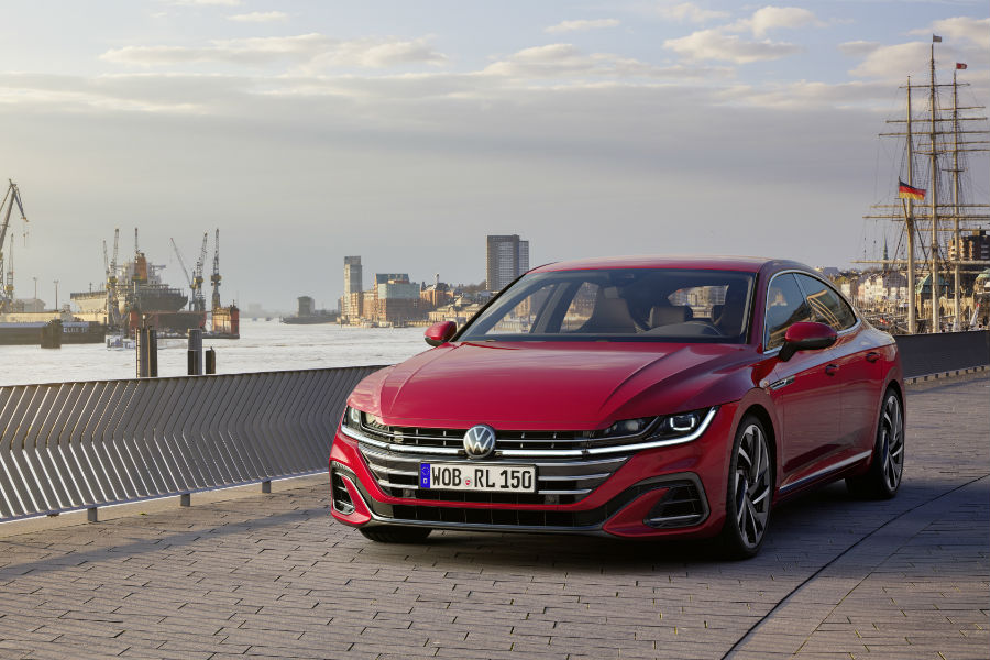 A head-on photo of the 2021 Volkswagen Arteon parked by a shipping port.