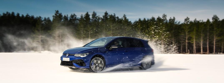 A dynamic photo of the 2022 Volkswagen Golf R sliding through snow.
