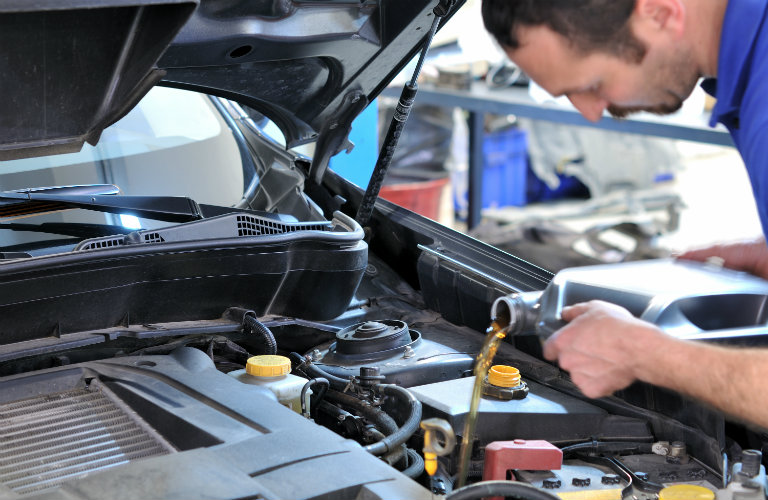 man putting oil into car engine